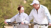 ciclista : Senior man riding a bike up to his wife and embracing her