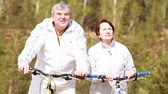 cyklus : Senior couple standing with their bikes and looking at something