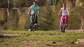 seasonal : Two young people cycling by the pit Stock Footage