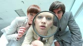 lente : Group of business people looking through magnifying glass