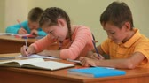 classmates : Three little children writing tests in school Stock Footage