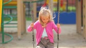 playful : Little girl swinging at the playground