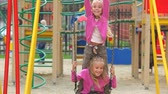empurrando : Mother pushing her daughters on swings