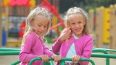 roundabout : Little twin girls posing on carousel