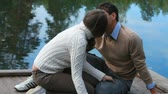 closeness : Young couple sitting on pier and kissing