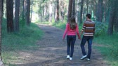 vínculo : Rear view of couple walking in forest holding hands