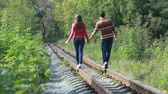 vínculo : Young couple walking along railroad in wood