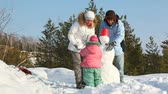 сугроб : Family of three spending time outdoors making a snowman