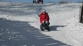 seasonal : Girl on a sledge pushed down a steep slope bumps into camera