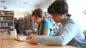 intelligent : Boy and girl studying at library then looking at camera