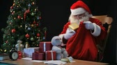 natal : Santa putting wrapped presents into his sack