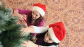 weihnachten : Two girls decorating fir-tree then waving at camera