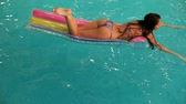 piscina : Young woman floating on an air bed in the swimming pool