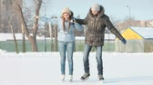 desportivo : Guy helping his girlfriend to learn how to skate