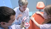 klinika : Dentist and his assistant showing a jaw model to a little girl and explaining how it functions