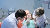 staff : Dentist and his assistant treating a little scared patient