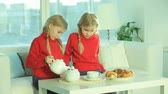 школьница : Twin girls having tea with croissants at home