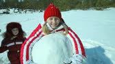 śnieżka : Smiling girl in winterwear hugging a huge snowball and looking at camera together with her little sister