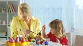 escova : Mom and her cute little daughter painting Easter eggs together for a coming holiday Stock Footage