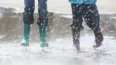 chuva : Boy and girl having fun on a rainy day jumping and dancing in puddle