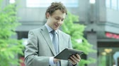 employee : Businessman working on digital pad then looking at camera and smiling, good for advertising Stock Footage