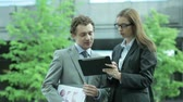 şirket : Business partners using a digital pad outdoors looking for business solutions