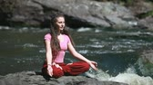 margem do rio : Peaceful young woman sitting in lotus pose on the bank of the mountain river