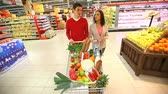 cart : Young couple pushing shopping cart full of groceries through huge mall