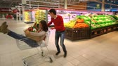 supermarket : Guy riding a market cart, his girlfriend sitting inside Stock Footage