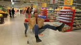 passeio : Young people taking a ride in a shopping trolley through a huge empty supermarket Stock Footage