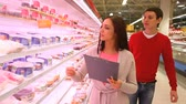 supermarket : Positive couple walking along the shelves in mall looking for necessary products