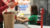 supermarket : Close-up of a customer being serviced by a sweet female cashier