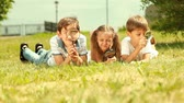 curiosidade : Three cute kids lying on the grass and looking playfully through magnifying glass Stock Footage