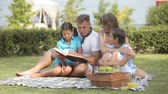 parentalidade : Father reading a book to his kids on a summer picnic