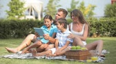 комфорт : Family of four communicating using digital tablet, summer picnic series Стоковые видеозаписи