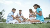 jogos de azar : Lovely family of four playing cards outdoor on a summer day Stock Footage