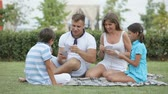 jogos de azar : Parents and kids sitting on the grass and playing cards