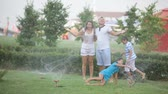 refrescante : Cheerful family enjoying freshness of the sprinkled water on a hot summer day Vídeos