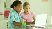 curiosidade : Modern schoolkids spending their free time in front of the laptop having fun Stock Footage