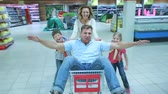 supermarket : Mom and two kids wheeling daddy in the market cart