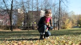 безмятежность : Lovely girl being deep in thought picking autumn leaves in city park
