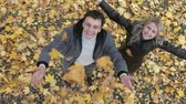 женский : Close-up of a smiling couple throwing fallen leaves up in the air