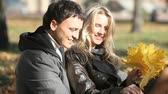 flirty : Couple sitting in park gathering a bunch of golden maple leaves