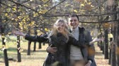 carinho : Adorable couple having fun throwing handfuls of golden leaves in the air