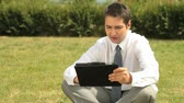confiança : Young office worker with touchpad considering business options outdoors