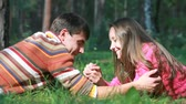 querido : Lovers lying on the grass exchanging tender touches Stock Footage