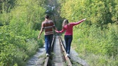 amor : Guy and girl holding hands following the railways leading through the park, conceptual footage Stock Footage