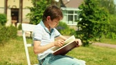 passatempo : Schoolboy reading a book from his holiday task list on a nice summer day Stock Footage