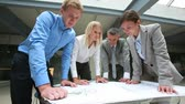 corporation : Team of architects taking a close look at the blueprint Stock Footage