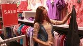 женский : Beautiful female shoppers looking for stylish garments on a sales day